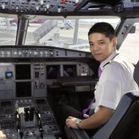 Earning his wings: Ryoji Fujii (right), a rookie pilot for Peach Aviation, prepares to fly a jet under the tutelage of a qualified captain at Kansai International Airport last month. | KYODO
