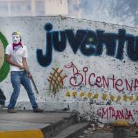 A masked anti-government protester holds a piece of metal during clashes with security forces in Caracas on Saturday.   AP