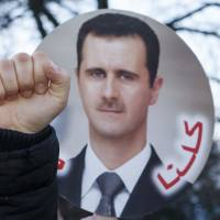 Holding hope: A demonstrator raises a fist in front of a photo of Syrian President Bashar Assad near the site of the 'Geneva II' peace talks in Montreux, Switzerland, on Jan.22. The international conference aimed at ending the country's brutal conflict, which has so far claimed more than 136,000 lives. | AP