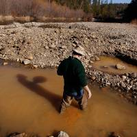 Lee Jones of Nevada prospects for gold on Jan. 26 along the Bear River near Colfax, California. | AP