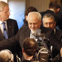 Aiming for trust: Iranian Foreign Minister Mohammad Javad Zarif (center) stands next to Swedish Foreign Minister Carl Bildt (left) prior to a panel discussion at the 50th Security Conference on security policy in Munich on Sunday. | AP