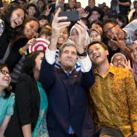 Secretary of State John Kerry takes a selfie with a group of students before delivering a speech on climate change Sunday in Jakarta. | AP