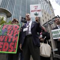 In business: Medical marijuana demonstrators hold up signs outside of the Federal Courthouse in Sacramento, California, last May. | AP