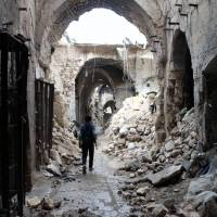 A rebel fighter walks in a devastated alley in the northern Syrian city of Aleppo, which has been devastated by the civil war, on Thursday. | AFP-JIJI