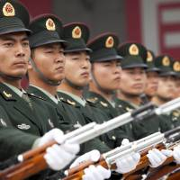 Face of the nation: People's Liberation Army soldiers are seen during a July 2011 media tour in Beijing.BLOOMBERG