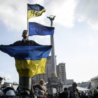 A man holds a Ukrainian flag as he stands in Independence Square, Kiev, on Monday after an arrest warrant was issued for ousted President Viktor Yanukovych for the 'mass murder' of protesters.   AFP-JIJI