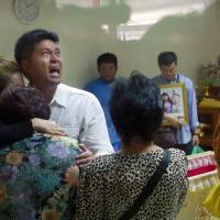 The father of two children killed a bomb attack on an anti-government protest site in Bangkok on Sunday is embraced by family members as he breaks down while visiting a hospital to collect their bodies Monday. | AP