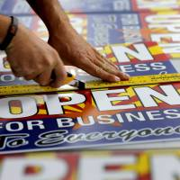 An employee at a store in Phoenix on Wednesday cuts signs opposing a Republican state bill that set off a national debate over gay rights, religion and discrimination. Arizona Gov. Jan Brewer vetoed the legislation later on Wednesday. | AP