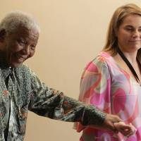 Generous will: Former South African President Nelson Mandela leaves his office in Johannesburg with Mandela Rhodes Foundation spokeswoman Zelda la Grange in Johannesburg on March 4, 2008. | AFP-JIJI