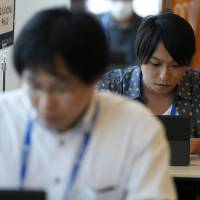 Cyberwarriors: Attendees work on computers as they participate in a 'capture the flag' competition during the SECCON 2013 computer security contest in Yokohama last August. A government-backed technology institute detected 12.8 billion cyberattacks in Japan last year — the most since surveys began in 2005. | BLOOMBERG
