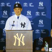 Welcome to the Big Apple: Yankees pitcher Masahiro Tanaka speaks during his introductory news conference as manager Joe Girardi listens on Tuesday in New York. | KYODO