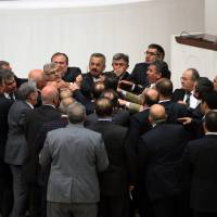 Turkey shoot?: Lawmakers from Turkish Prime Minister Recep Tayyip Erdogan's ruling party and the opposition Republican People's Party brawl during a tense all-night debate over controversial reforms tightening government control over the judiciary, in Ankara on Saturday. | AP