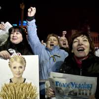 An opposition protester holds a picture of newly freed Ukrainian opposition leader Yulia Tymoshenko as the former prime minister delivers a speech at a rally in Kiev's Independence Square on Saturday. | AFP-JIJI