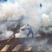 A Venezuelan demonstrator hurls a teargas canister back toward government forces during an attempted blockade of a major highway in Caracas on Thursday. | AP