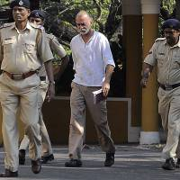 Former editor of Tehelka, Tarun Tejpal (center) is escorted by Indian police as he leaves the high court after his bail hearing in Panaji on Tuesday. The editor, who is charged with raping a colleague, has repeatedly protested his innocence in the case, which has dominated local media. | AFP-JIJI