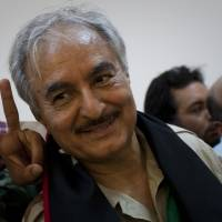 Coup de grace: Khalifa Hifter, then a senior Libyan rebel commander, leaves a news conference in Benghazi in March 2011.   AP
