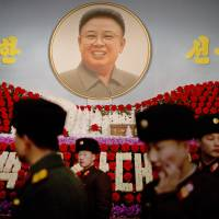 North Korean soldiers walk past a portrait of the late leader Kim Jong Il during a flower exhibition in Pyongyang on Feb. 16. | AP