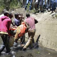 The body of an illegal miner is carried after being pulled out of an illegal gold mine in Benoni, near Johannesburg, on Tuesday. South Africa's elite police unit have vowed to hunt down illegal mining kingpins Tuesday after two bodies were discovered at an abandoned gold mine where dozens of people had been trapped. | AFP-JIJI