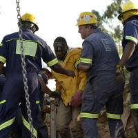 Rescuers tend to one of the 11 workers (center) that were rescued from an illegal gold mine near Johannesburg, South Africa, on Sunday. The accident is the second to hit the country's mining industry in as many weeks. | AFP