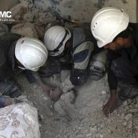 Dust to dust: Syrian rescue workers dig out the lifeless body of a young child from the rubble of a building damaged by Syrian regime attacks in Aleppo on Sunday. | AP