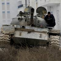 Meeting opposition: Syrian opposition fighters drive a tank during clashes with government forces on the outskirts of the northern city of Aleppo on Monday.   AFP-JIJI