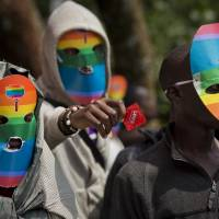 Gay Kenyan men and women, along with others supporting their cause, stage a rare protest against Uganda's increasingly tough stance against homosexuality outside the Uganda High Commission in Nairobi on Feb 10. They are wearing masks to preserve their anonymity, and one is holding a condom. | AP