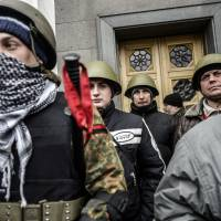 Protesters belonging to the 'Maidan Self-Defense Group' guard the Ukrainian parliament on Thursday in Kiev. | AP