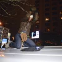 Ukrainian journalist Tetyana Chernovil, who has been tapped as head of an anti-corruption committee in the new government, beats the roof of a police minivan with a stone during a pro-European Union rally in Kiev on Nov. 25. In December, she was was beaten by a group of unknown assailants outside Kiev. | AP