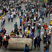 Demonstrators roll a water pipe in an attempt to block a major highway during clashes with the Bolivarian National Guard in Caracas on Thursday. | AP