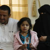 Afnan, age 6, holds a picture of her father, Bandar al-Hassani, who was killed in a U.S. drone strike last year, on Feb. 14. Beside her are her grandparents Omar al-Hassani and Khadija Hassan. Beside Bandar, the couple have lost two more sons: one in another U.S. drone strike in 2013 and one during fighting between al-Qaida militants and government forces in 2012.   AP