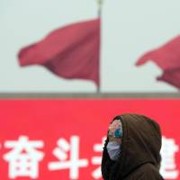 A woman wearing a protective mask walks through Tiananmen Square during a hazy day in Beijing on Feb. 13. The city issued a rare 'orange' alert Friday, the second-highest of the four levels of urgency, prompting health advisories and bans on barbecues, fireworks and demolition work, but no order to pull cars from the streets.   AP
