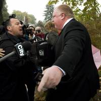Patience cracks: Toronto Mayor Rob Ford tells reporters to get off his property as he leaves his home in Toronto on Oct. 31.   AP