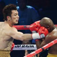 On target: Middleweight Ryota Murata punches Brazilian Carlos Nascimento in the head during the third round of Saturday's bout in Macau. | KYODO