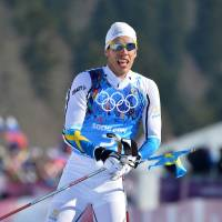 Swede success: Sweden's Marcus Hellner waves his country's flag as he crosses the finish line to win the men's 4x10-km cross country relay at the Sochi Olympics on Sunday. | AFP-JIJI