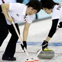 Working together: Michiko Tomabechi (left) and Yumie Funayama sweep the ice for Japan during a women's curling competition against South Korea on Tuesday in Sochi, Russia. | AP