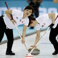 Day of disappointment: Japan's Chinami Yoshida (left) and Kaho Onodera sweep the ice against Britain in the women's curling competition on Friday in Sochi, Russia. Japan lost 12-3. | AP