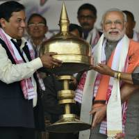 State president of India's main opposition Bharatiya Janata Party in Assam, Sarbananda Sonowal (left), presents an Assamese Sarai, an Assamese souvenir, to the party prime ministerial candidate and Gujarat state Chief Minister Narendra Modi (center) during a public rally in Gauhati on Saturday. | AP