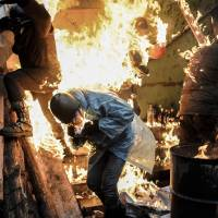 Protesters burn as they stand behind barricades during clashes with police Thursday in Kiev. | AFP-JIJI