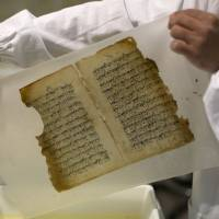 Shreds and tatters: An employee works on a restoration of an old manuscript at the al-Aqsa mosque compound library in Jerusalem. | AP
