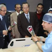Egyptian tourism minister Hesham Zazoua (left) and the South Korean ambassador in Cairo (center) visit a Korean tourist who was injured during an explosion that targeted a tourist bus, as he receives medical treatment in Sharm El-Sheik hospital late Sunday. | AP
