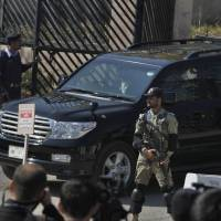 A paramilitary soldier stands guard as the vehicle of former Pakistani President Pervez Musharraf leaves after his court appearance in Islamabad on Tuesday. | AP