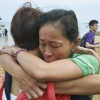 Members of a Japanese search party hug Monday after they received the news that survivors were found.  | KYODO
