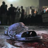 Indelible print: A victim's bloodstained shoe lies on the ground at the site of a grenade attack on a crowded movie theater that killed at least 13 in Peshawar, Pakistan, on Tuesday. | AP