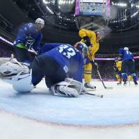 The path to victory: Sweden's Carl Hagelin scores against Slovenia goaltender Robert Kristan in the Olympic ice hockey quarterfinals on Wednesday at Bolshoy Ice Dome. | AFP-JIJI