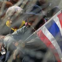 Anti-government protesters in Bangkok take positions behind barbed wire during a rally outside the office of the permanent secretary for defense where Thai Prime Minister Yingluck Shinawatra was reportedly working Monday. | AP