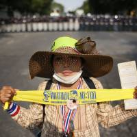 A lone anti-government protester holds a ribbon that reads 'king's soldier' in front of a line of riot police during a Tuesday standoff in Bangkok. Hundreds of riot police attempted to clear out anti-government protest sites around the capital Tuesday, triggering clashes that left three people dead and 57 others injured. | AP
