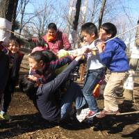 Kids in Tokyo's Kiba Park swing on a rope bridge, one of the activities available for free at Kiba Playpark.
