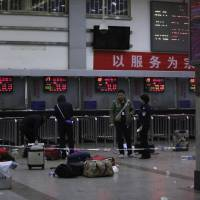 Police stand near luggage left at the ticket office after a group of armed men attacked people Saturday at Kunming railway station, Yunnan province. | REUTERS