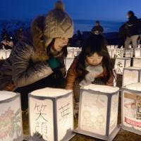 A mother and her daughter attend a candle-lighting event held Sunday to commemorate the third anniversary of the March 11 tsunami and earthquake in Natori, Miyagi Prefecture, one of the worst-hit areas.  | KYODO