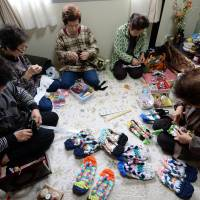 Elderly women making sandals from used T-shirts in a small room of a temporary housing complex in Ishinomaki, Miyagi Prefecture, on March 3, 2014.  | AFP-JIJI